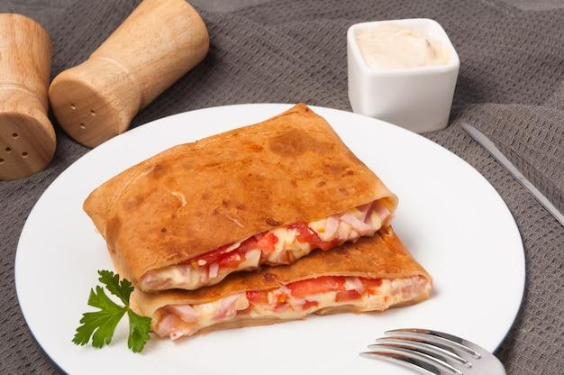 白い皿にハム、チーズ、トマトのパンケーキ。水平フレーム