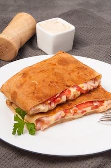 白い皿にハム、チーズ、トマトのパンケーキ。垂直フレーム