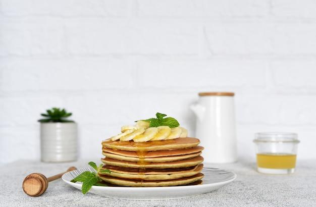 台所のテーブルで朝食に蜂蜜とバナナのパンケーキ。