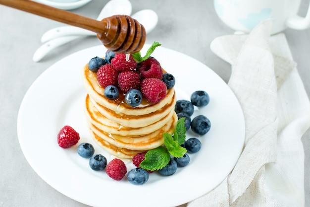 Блины с медом и ягодами на белом фоне