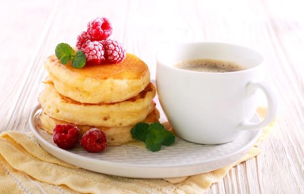 Блины с медом и малиной и чашка кофе