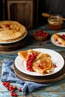白いプレートに蜂蜜と赤スグリのパンケーキmaslenitsa