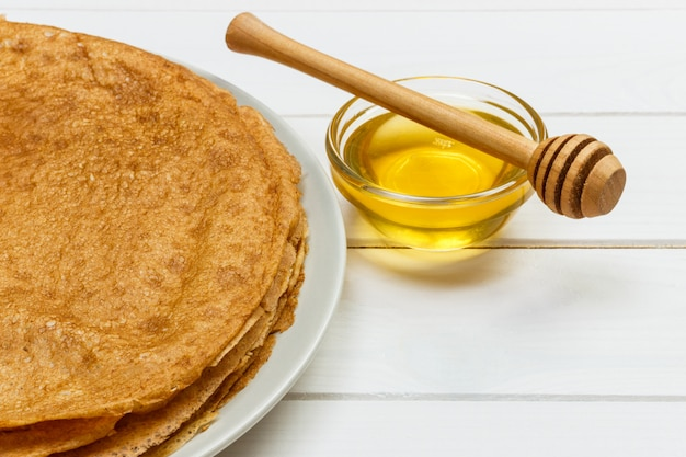 Pancakes with honey and butter on a wooden background