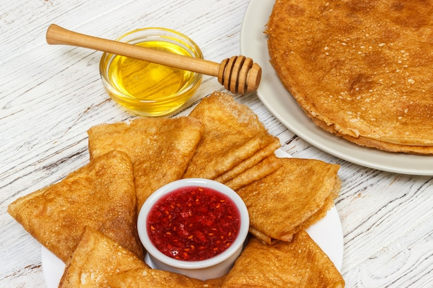 Pancakes with honey and jam on wood
