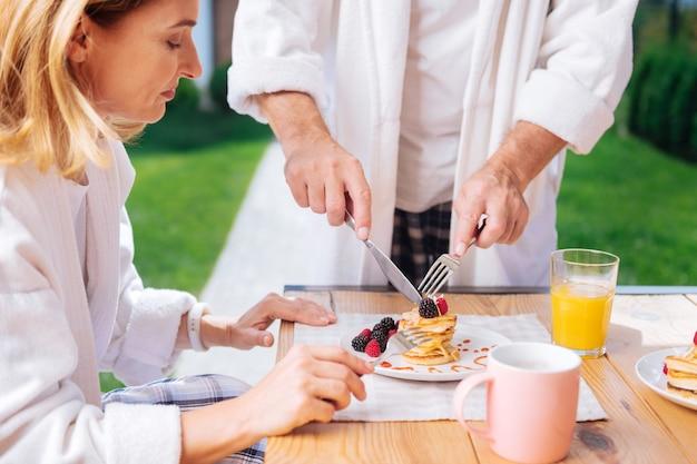 Блины с медом. зрелая привлекательная женщина в белом халате пробует теплые блины с медом на завтрак