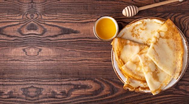 Блины с медом на тарелке. вид сверху,