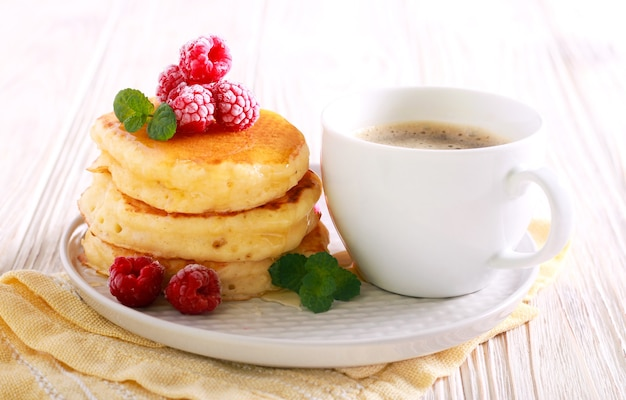 Pancakes with honey and raspberry and cup of coffee