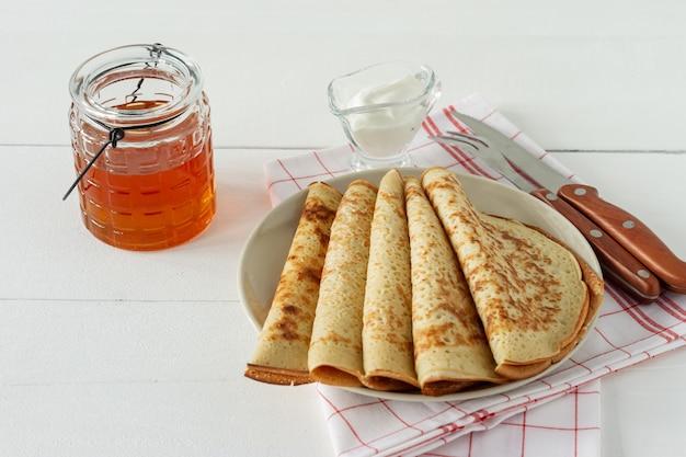 하얀 접시에 꿀 시럽을 얹은 팬케이크. 팬케이크 주간 또는 shrovetide를 위한 전통 크레이프.