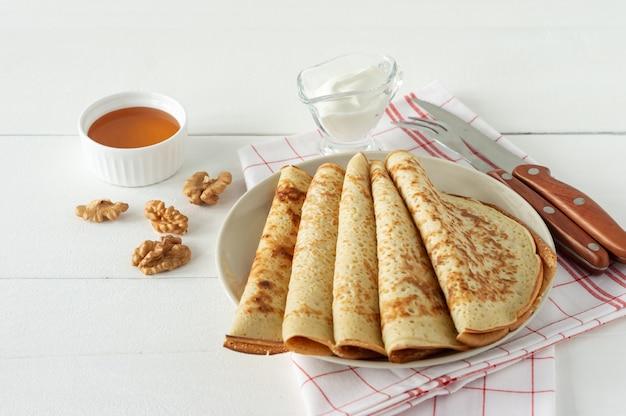 Блины с медовым сиропом на белой тарелке. традиционные блины на масленицу или масленицу.