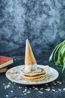 어두운 표면에 하얀 접시에 아이스크림 콘, 바나나, 코코아 가루 및 책을 넣은 팬케이크