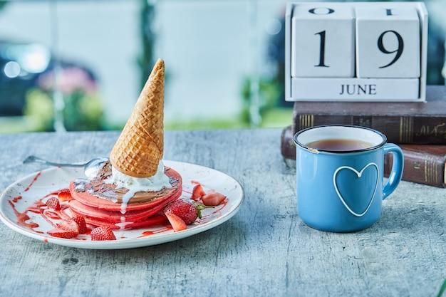 カレンダーと本の表面にアイスクリームコーン、イチゴ、熱いお茶が入ったパンケーキ