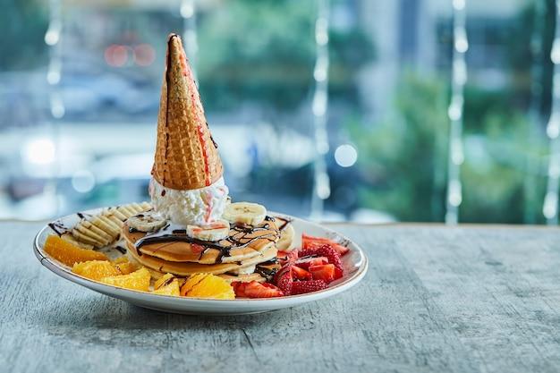 아이스크림 콘, 귤, 딸기, 바나나 및 초콜릿 시럽을 곁들인 팬케이크를 대리석 표면에 흰색 접시에 담았습니다.