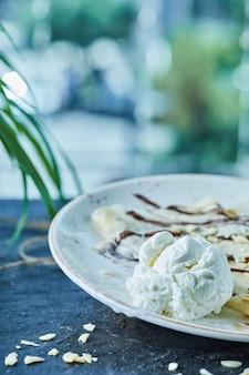 어두운 표면의 흰색 접시에 아이스크림, 뿌리, 초콜릿 팬케이크