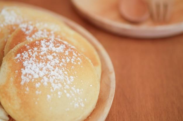 나무 접시에 설탕을 입힌와 팬케이크입니다. 달콤한 디저트.