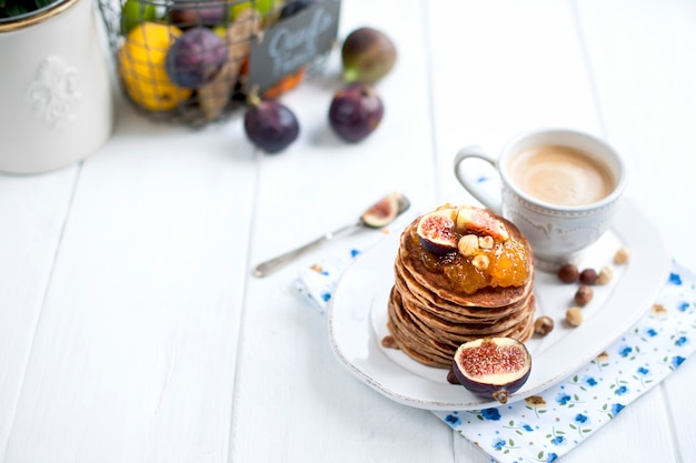 Pancakes with jam and figs on a white plate and a cup of coffee on a white background