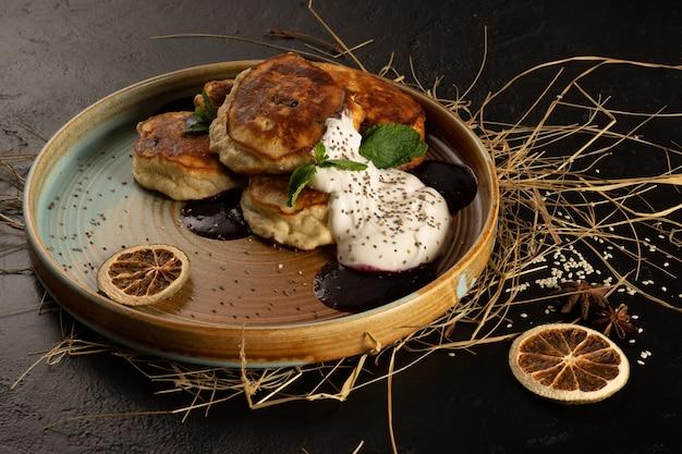丸い色のプレートにミントの葉、レモンスライス、スターアニスを添えたジャム、ヨーグルト、チアシードのパンケーキ。小麦粉のパンケーキの古典的なプロヴァンススタイルの朝食
