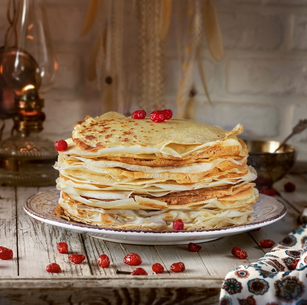 Pancakes with lace edges on a plate. next cherry berries.