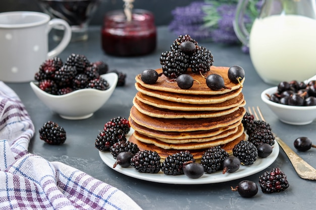 Pancakes with maple syrup, blackberries and currants are stacked on a plate