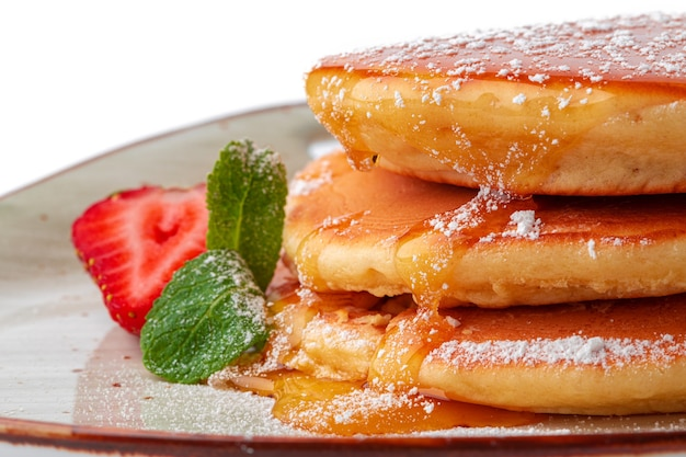 Pancakes with maple syrup on plate isolated on white
