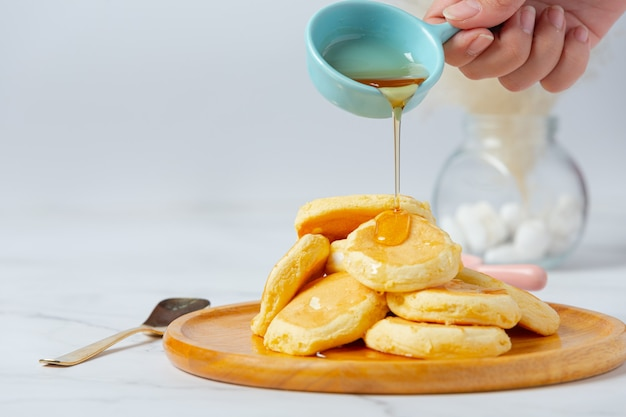 Pancakes with maple syrup in plate on white background