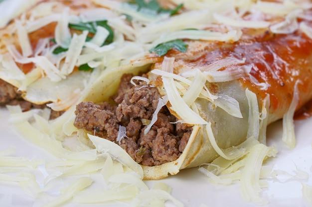 肉のパンケーキ、トマトソースとチーズ、コリアンダーと粉チーズを上に乗せたもの。