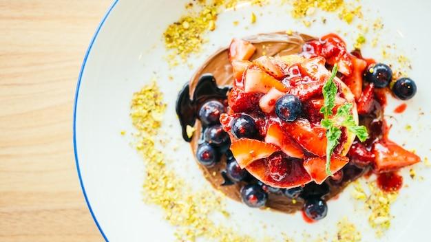 Блины со смешанными ягодными фруктами в белой тарелке