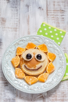 Pancakes with orange, grapes, and banana for kids