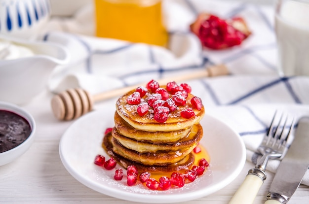 Pancakes with pomegranate seeds, honey and powdered sugar