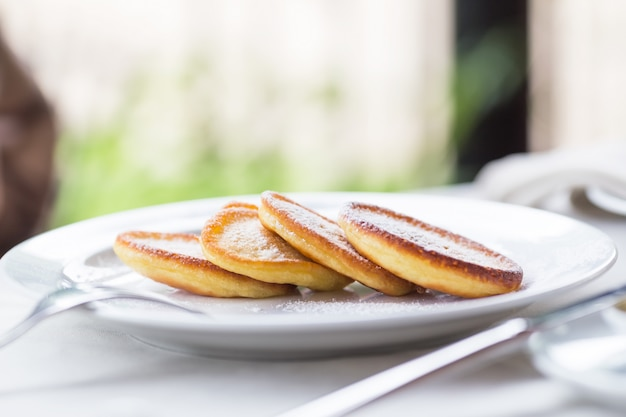 Pancakes with powdered sugar on a white plate