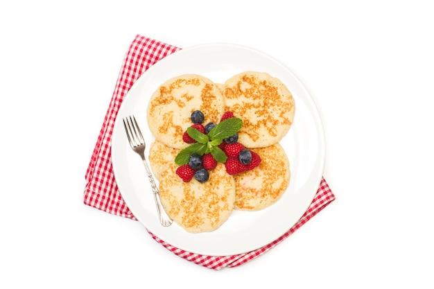 上面図の白いプレートと白い背景にラズベリーとブルーベリーのパンケーキ