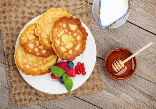 ラズベリー、ブルーベリー、ミント、ハニーシロップのパンケーキ。木製のテーブルの上