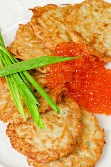 赤キャビアとネギのクローズアップ料理のパンケーキ