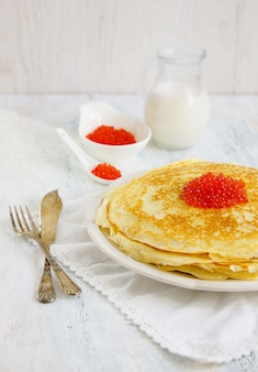 Pancakes with red caviar on the white background