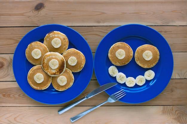 青いプレートと木製の背景に笑顔でパンケーキ。バナナフルーツ笑顔の朝食-子供のための楽しい食べ物