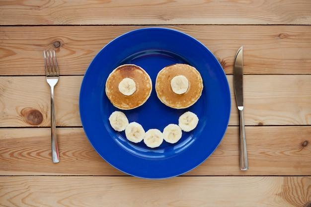 青いプレートと木製の背景に笑顔でパンケーキ。バナナフルーツの笑顔-子供のための楽しい食べ物