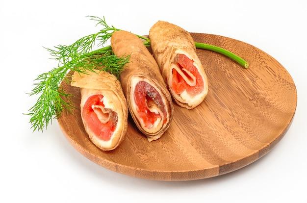 Блины с копченым лососем и сливочным сыром на тарелке.