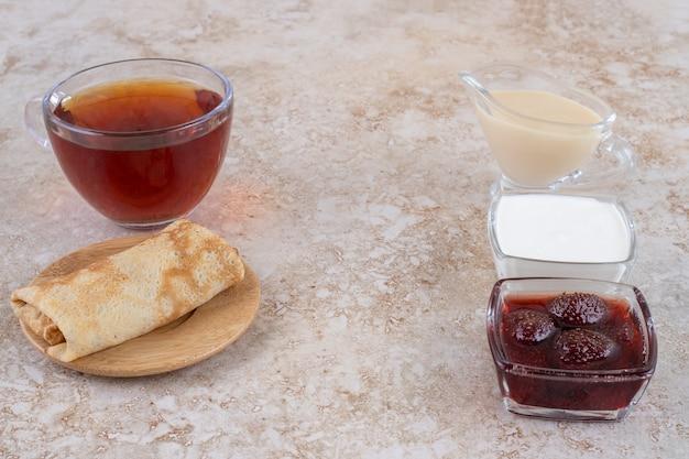 Frittelle con panna acida e una tazza di tè