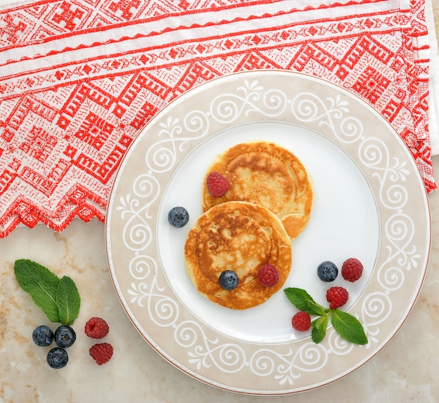 Pancakes with sour cream on the plate with berries