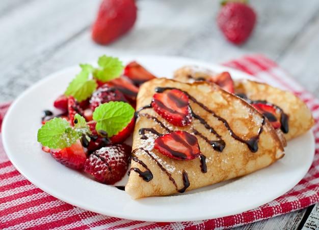 ミントの葉で飾られたイチゴとチョコレートのパンケーキ