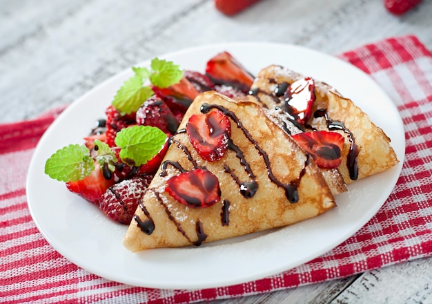 Pancakes with strawberries and chocolate decorated with mint leaf