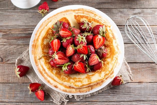딸기 클로즈업으로 팬케이크입니다. 마슬레니차. 딸기와 함께 얇은 갓 구운 팬케이크. 팬케이크 형태의 디저트. 평면도.
