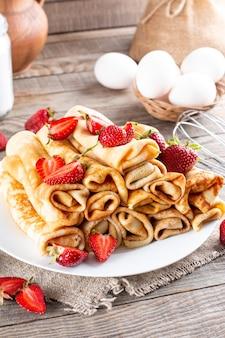 딸기 클로즈업으로 팬케이크입니다. 마슬레니차. 딸기와 함께 얇은 갓 구운 팬케이크. 팬케이크 형태의 디저트