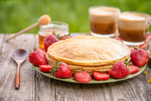 Pancakes with strawberries and coffee for breakfast.