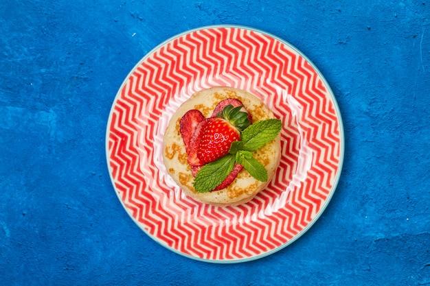 赤と白のプレートと古典的な青の背景にイチゴのパンケーキ