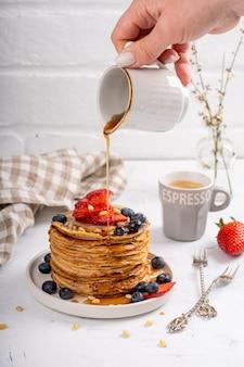 Блины с сиропом и ягодами на столе для завтрака