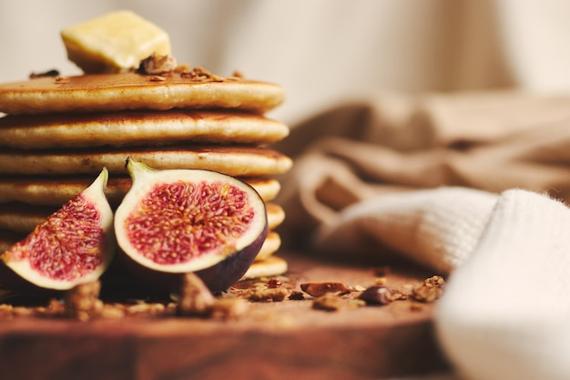 Pancakes with syrup, butter, figs and roasted nuts on a wooden plate