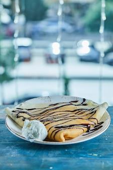 파란색 표면에 흰색 접시에 바닐라 아이스크림, 초콜릿 팬케이크