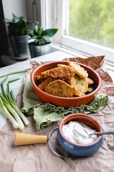 창가의 테이블에 요구르트 드레싱과 허브를 곁들인 호박과 양배추 팬케이크 프리미엄 사진