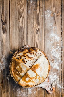 Pancakes on a wooden board from the upper angle