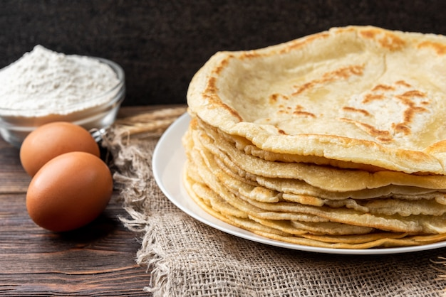 Pancakes on wooden table with ingredients beside